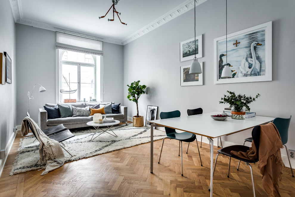 Example of a mid-sized danish formal and open concept light wood floor living room design in Stockholm with gray walls and no tv