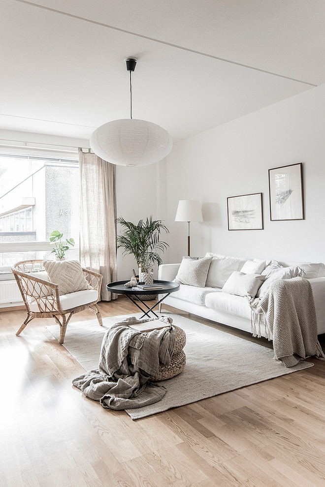 Mid-sized danish enclosed and formal beige floor and light wood floor living room photo in Stockholm with white walls