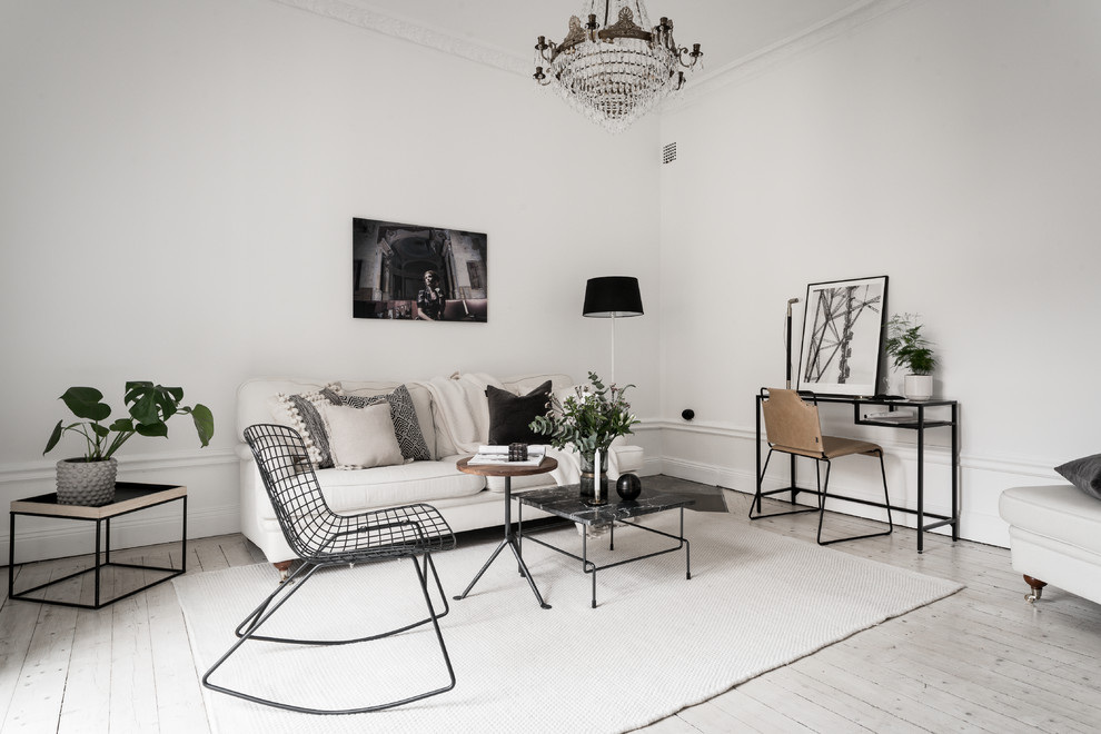 Example of a danish formal light wood floor and beige floor living room design in Stockholm with white walls