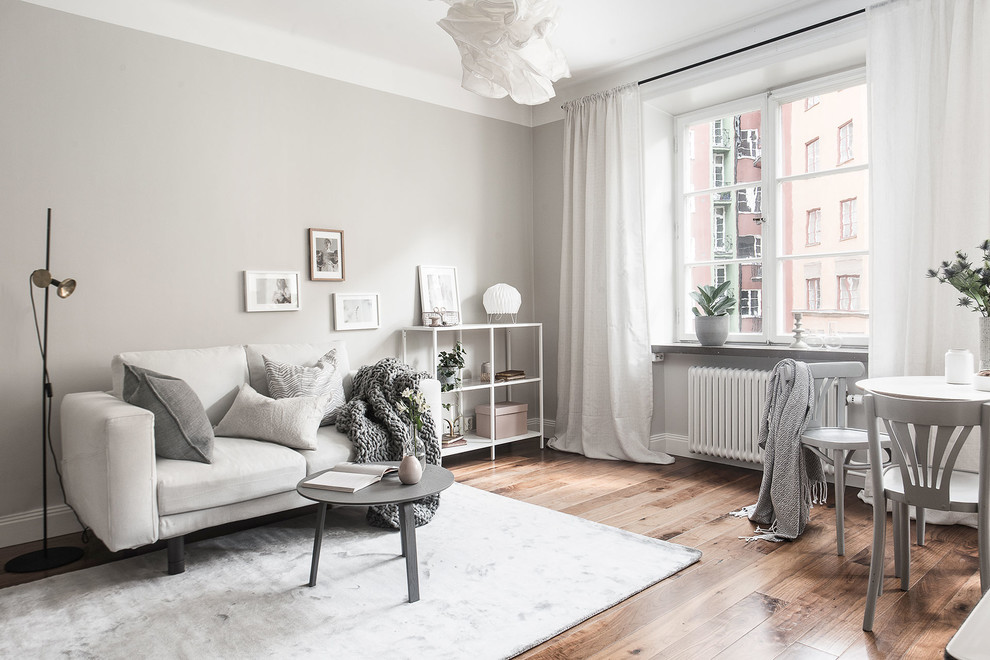 Inspiration for a scandinavian open concept medium tone wood floor living room remodel in Stockholm with gray walls