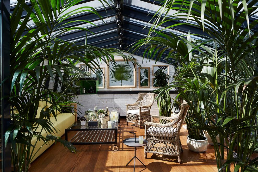 Sunroom - mid-sized contemporary medium tone wood floor sunroom idea in Paris with a skylight