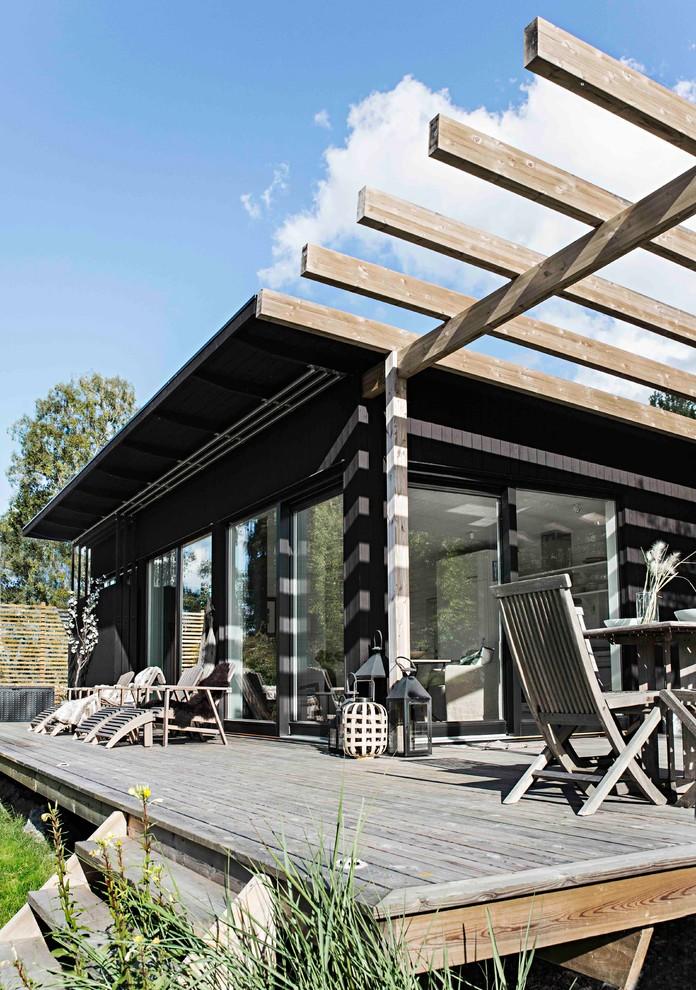 Bild på en mellanstor nordisk veranda på baksidan av huset, med trädäck och en pergola