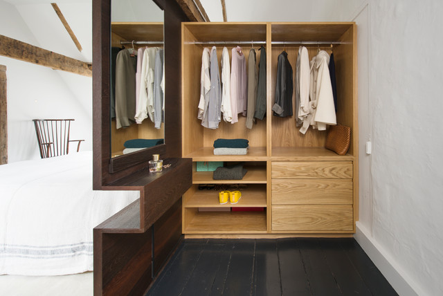 Inspiration for a medium sized contemporary gender neutral dressing room in Sussex with painted wood flooring, black floors, open cabinets and light wood cabinets.