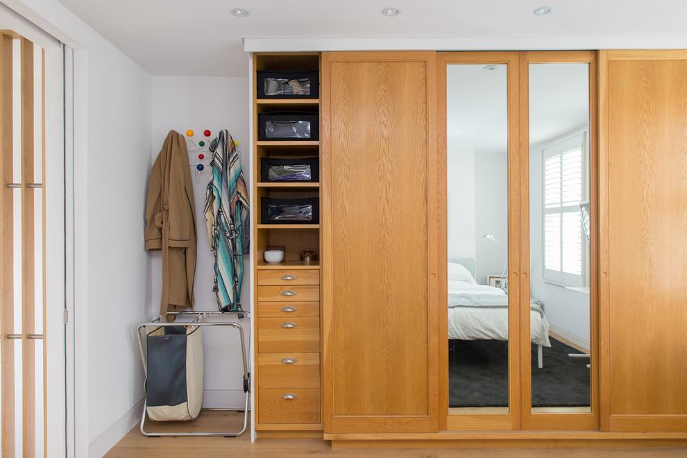 На фото: шкаф в нише унисекс в современном стиле с фасадами с утопленной филенкой, фасадами цвета дерева среднего тона и светлым паркетным полом
