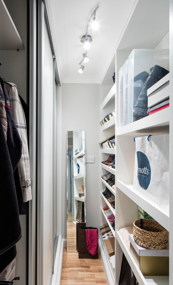 Small minimalist gender-neutral medium tone wood floor walk-in closet photo in Dublin with flat-panel cabinets and white cabinets