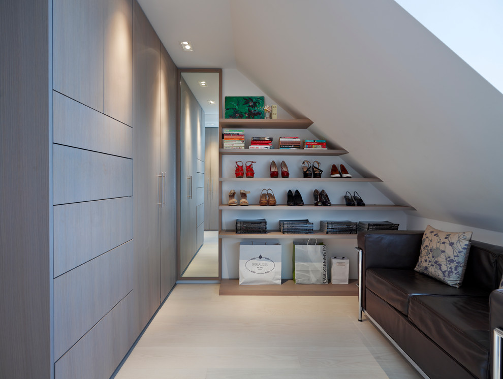 Example of a light wood floor dressing room design in London with flat-panel cabinets and gray cabinets