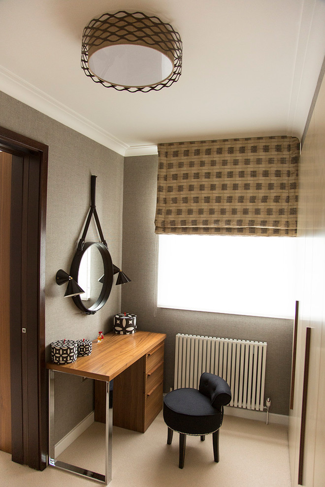 Small trendy gender-neutral carpeted walk-in closet photo in London with flat-panel cabinets and beige cabinets