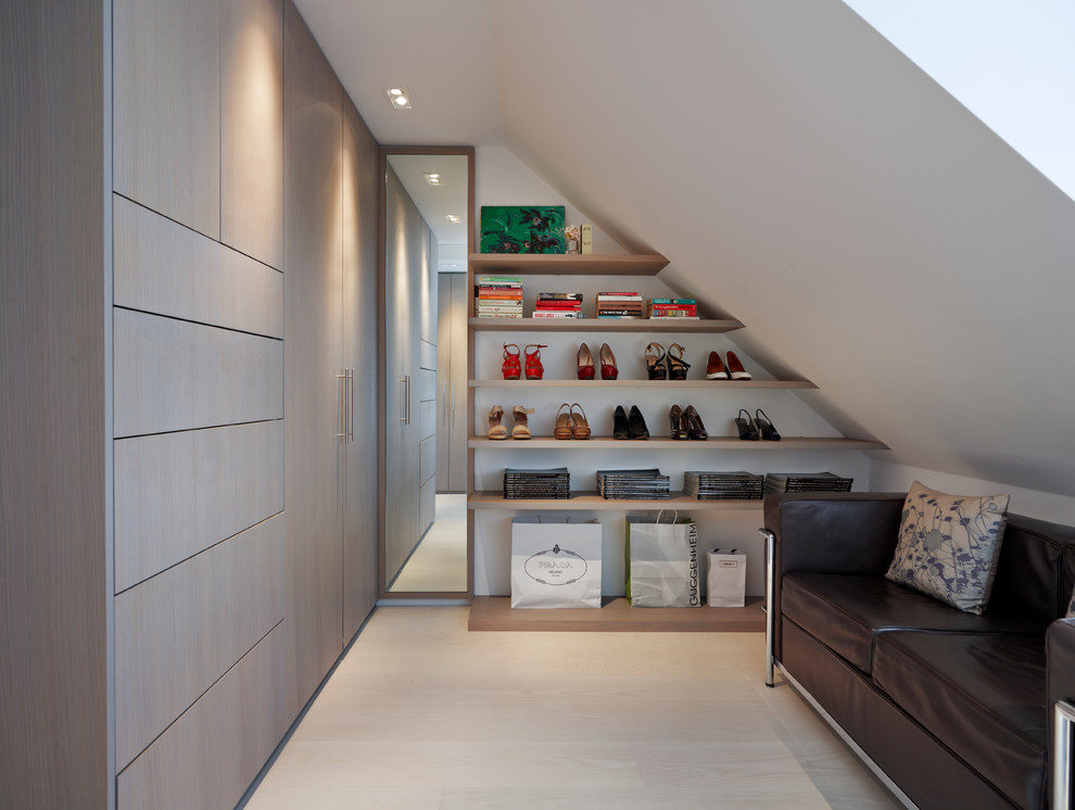 Dressing room - contemporary gender-neutral light wood floor dressing room idea in London with flat-panel cabinets and light wood cabinets
