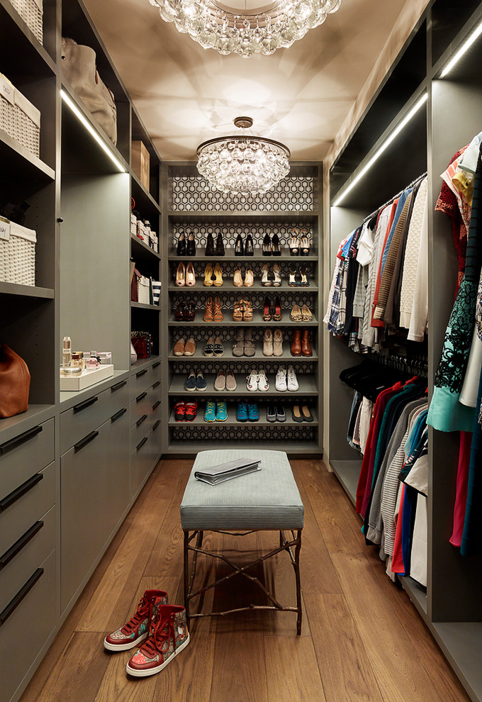 Inspiration for an eclectic women's medium tone wood floor and brown floor walk-in closet remodel in San Francisco with flat-panel cabinets and green cabinets