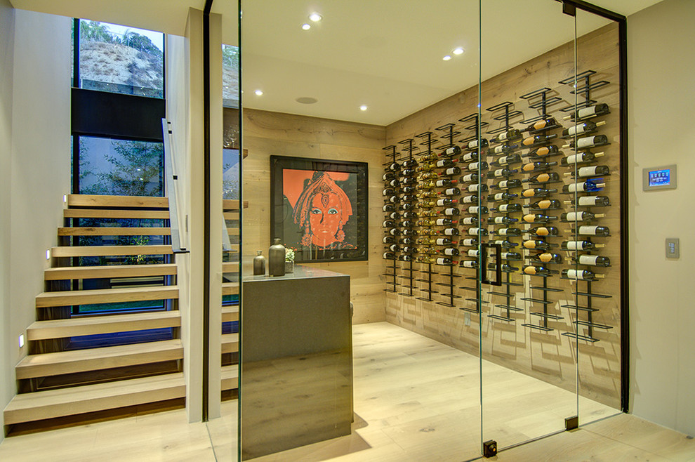 Inspiration for a modern light wood floor and white floor wine cellar remodel in Los Angeles with display racks