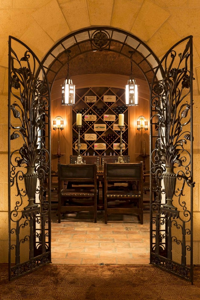 Inspiration for a large mediterranean terra-cotta floor wine cellar remodel in Denver with diamond bins