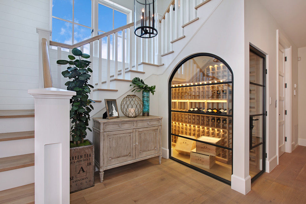 Inspiration for a coastal medium tone wood floor and yellow floor wine cellar remodel in Orange County with storage racks