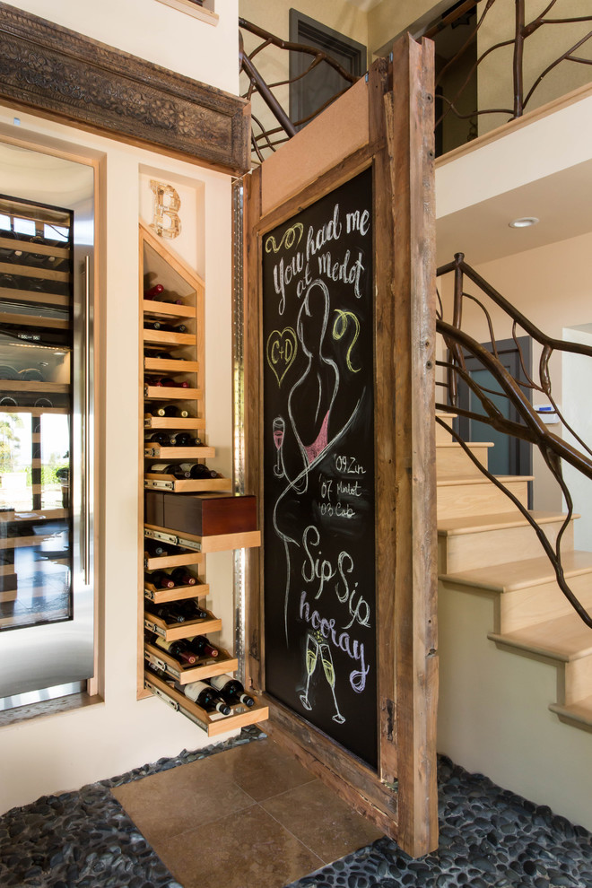 Wine cellar - large eclectic travertine floor wine cellar idea in Los Angeles with storage racks