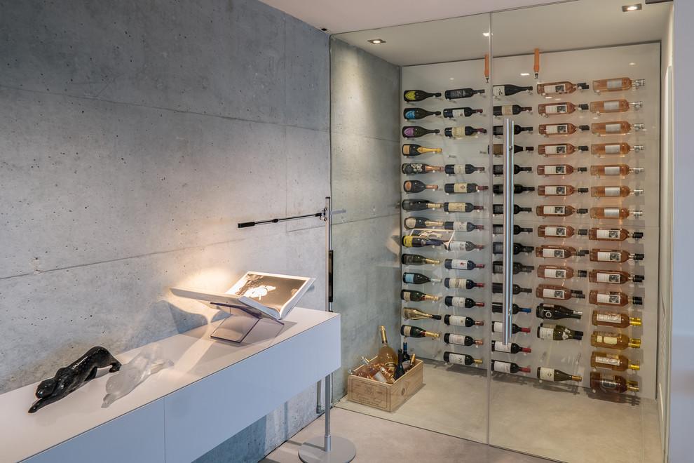 Idee per una cantina design con pavimento in cemento, portabottiglie a vista e pavimento grigio