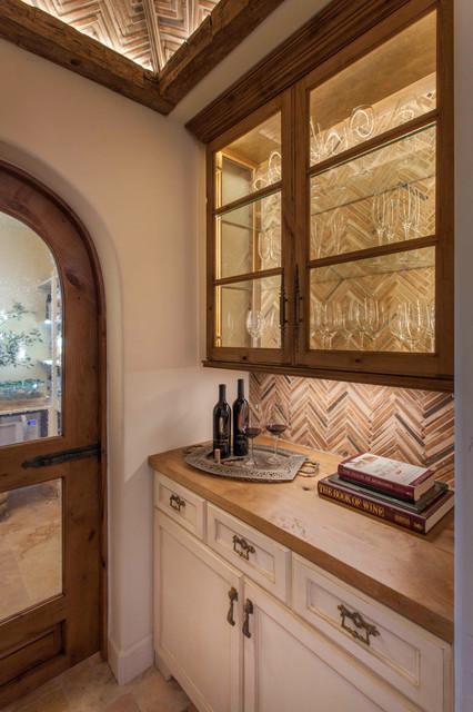 Wine cellar - mid-sized mediterranean limestone floor and beige floor wine cellar idea in San Diego