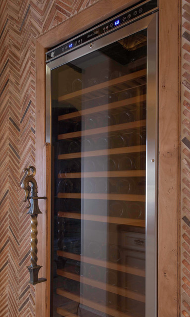 Example of a mid-sized tuscan limestone floor and beige floor wine cellar design in San Diego