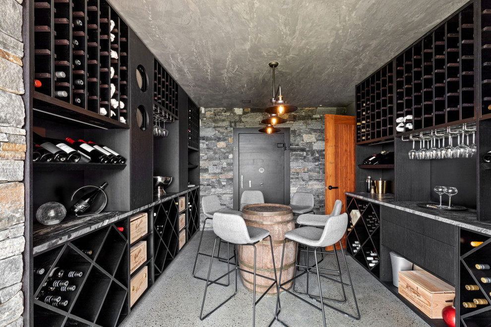 This is an example of a mid-sized contemporary wine cellar in Sunshine Coast with concrete floors, grey floor and display racks.