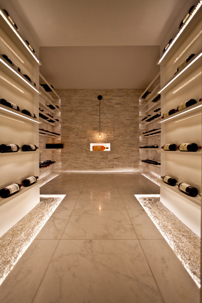 Inspiration for a large contemporary marble floor wine cellar remodel in Toronto with display racks