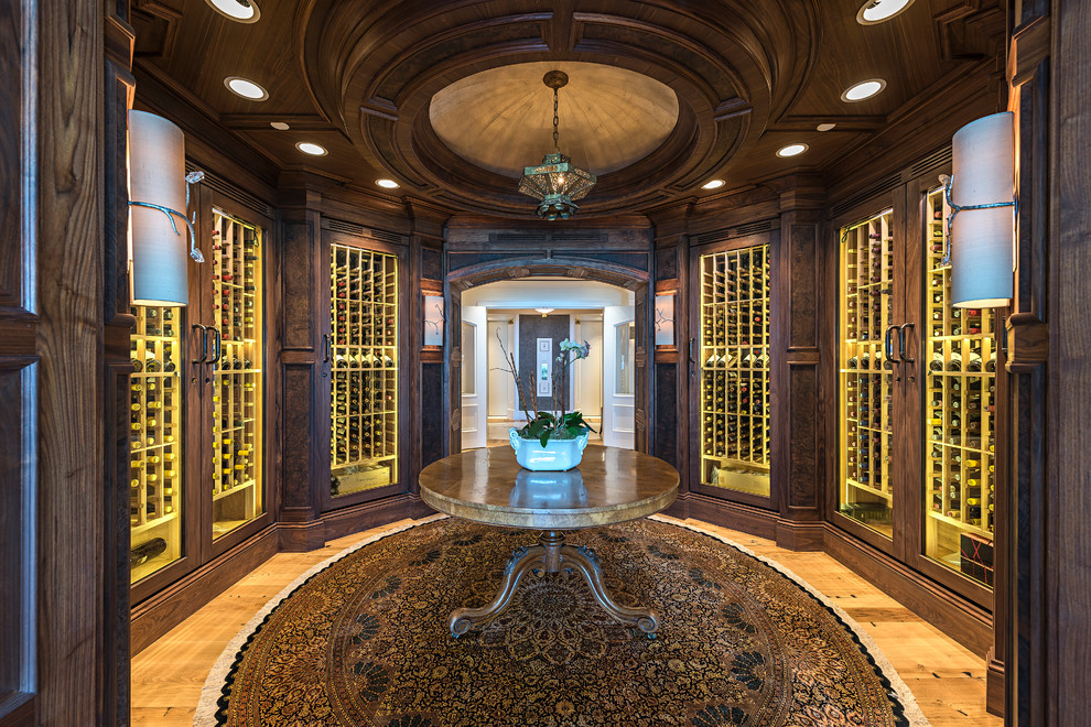 Example of an ornate light wood floor and brown floor wine cellar design in Miami with display racks