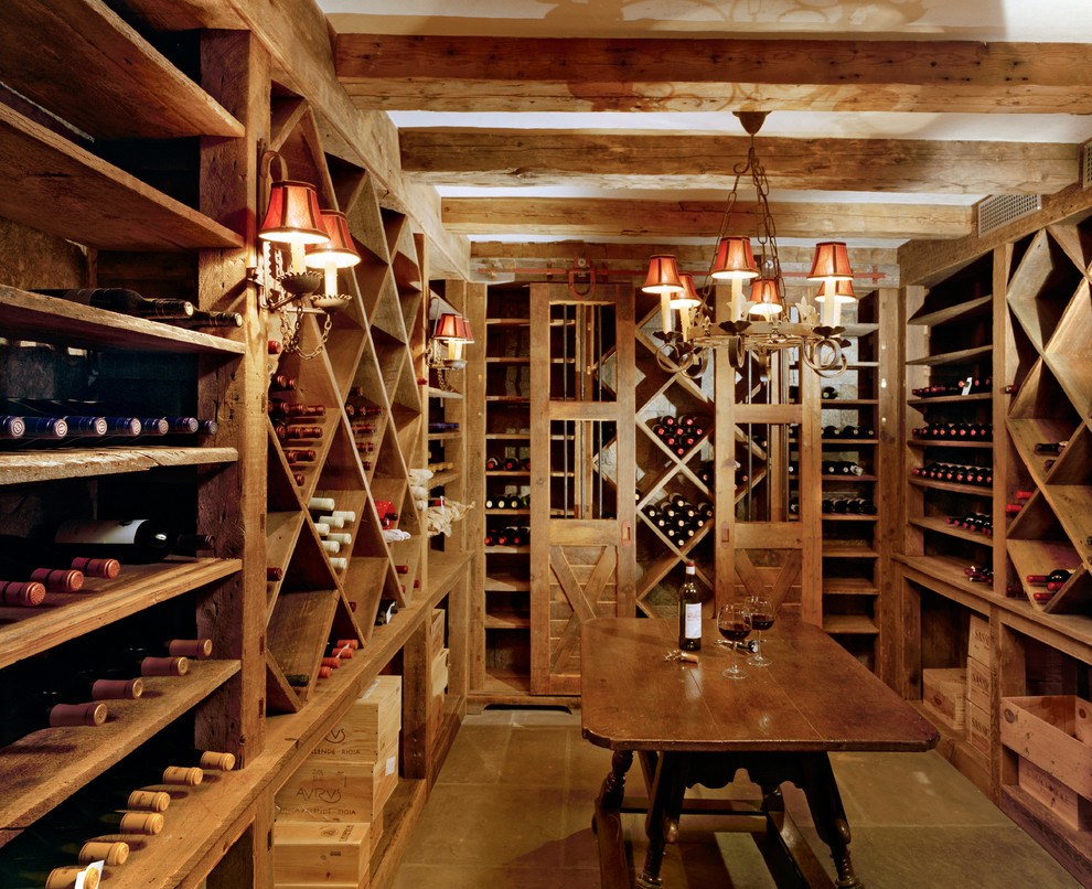 Large country porcelain floor and brown floor wine cellar photo in New York with storage racks