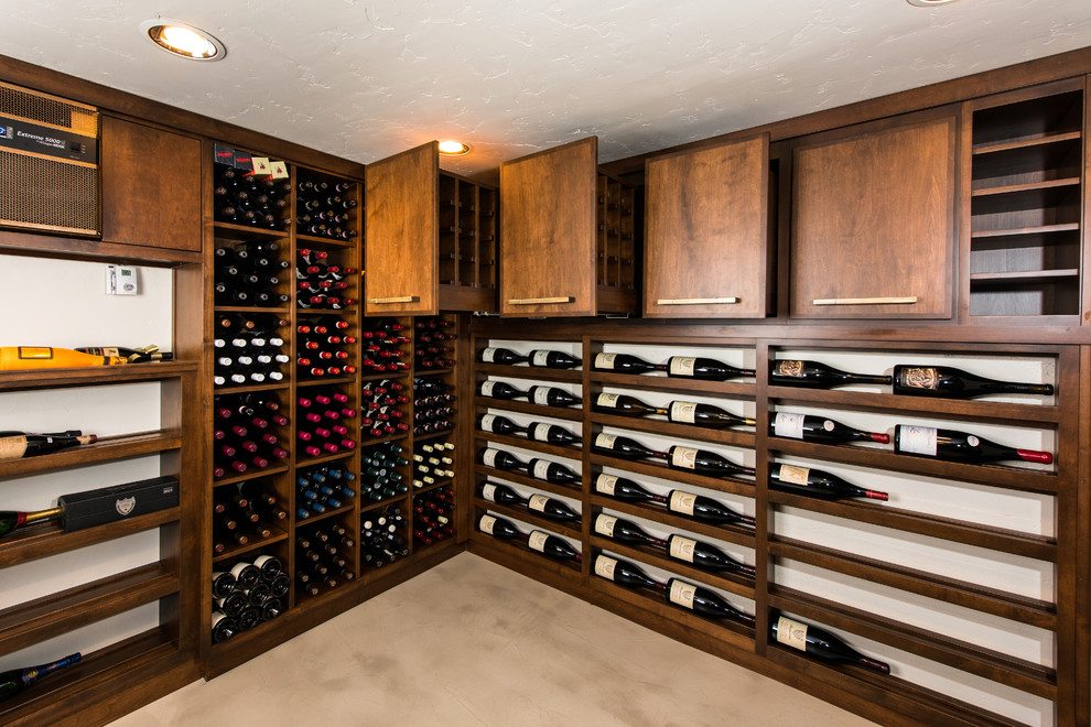 Inspiration for a mid-sized timeless concrete floor and beige floor wine cellar remodel in Other with storage racks