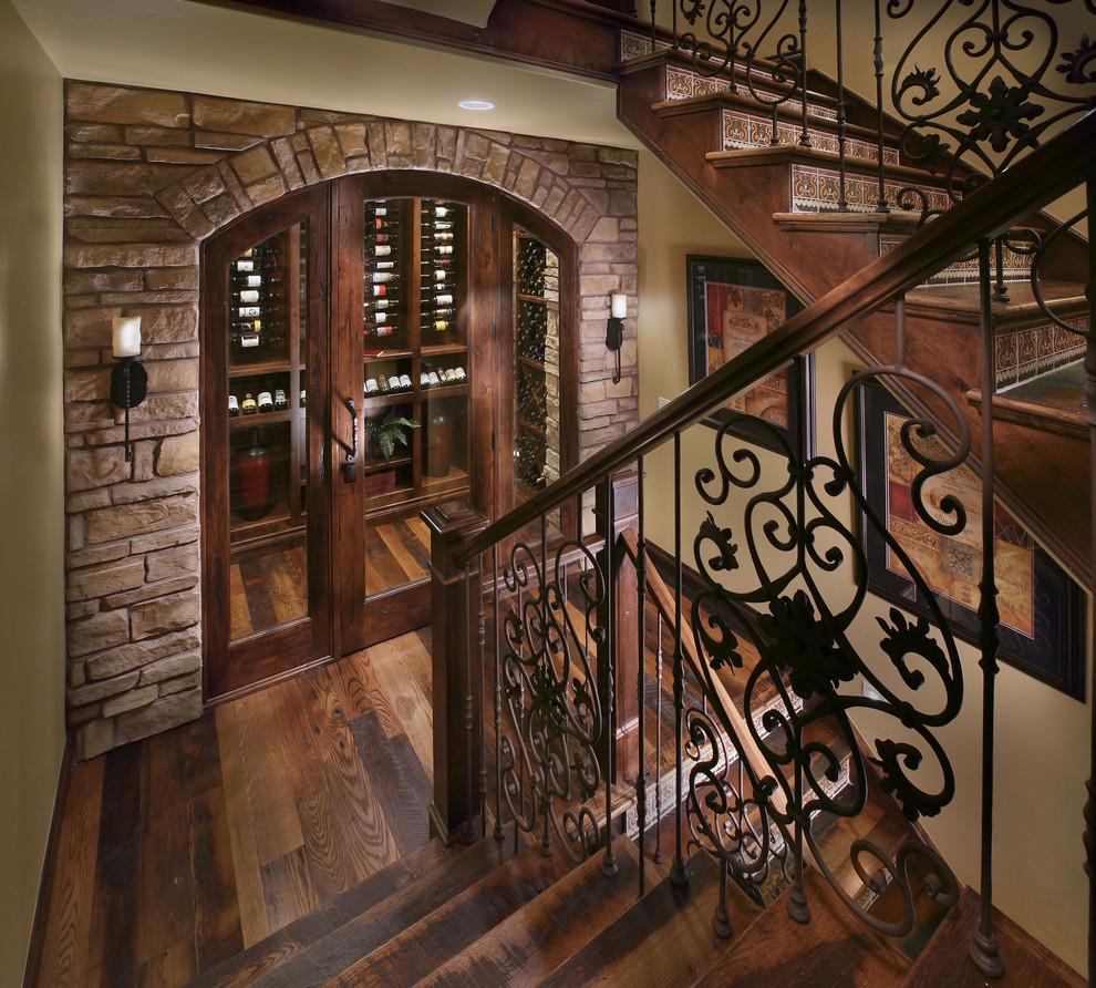 Inspiration for a mediterranean dark wood floor wine cellar remodel in Denver with display racks