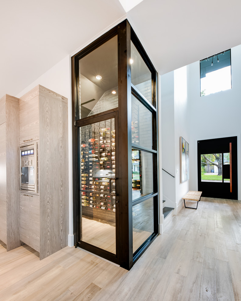Inspiration for a mid-sized contemporary light wood floor and beige floor wine cellar remodel in Dallas with storage racks
