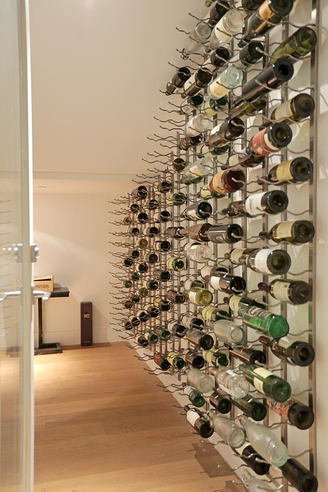 Inspiration for a mid-sized modern medium tone wood floor wine cellar remodel in Los Angeles with display racks