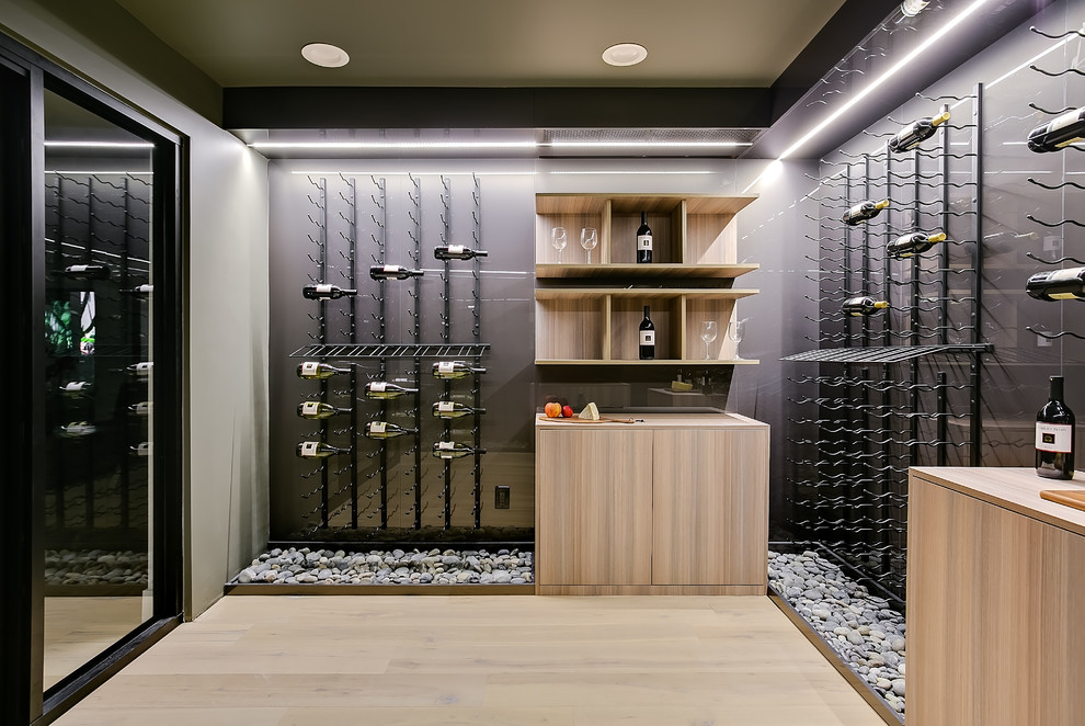 Inspiration for a mid-sized contemporary light wood floor and beige floor wine cellar remodel in Los Angeles with storage racks
