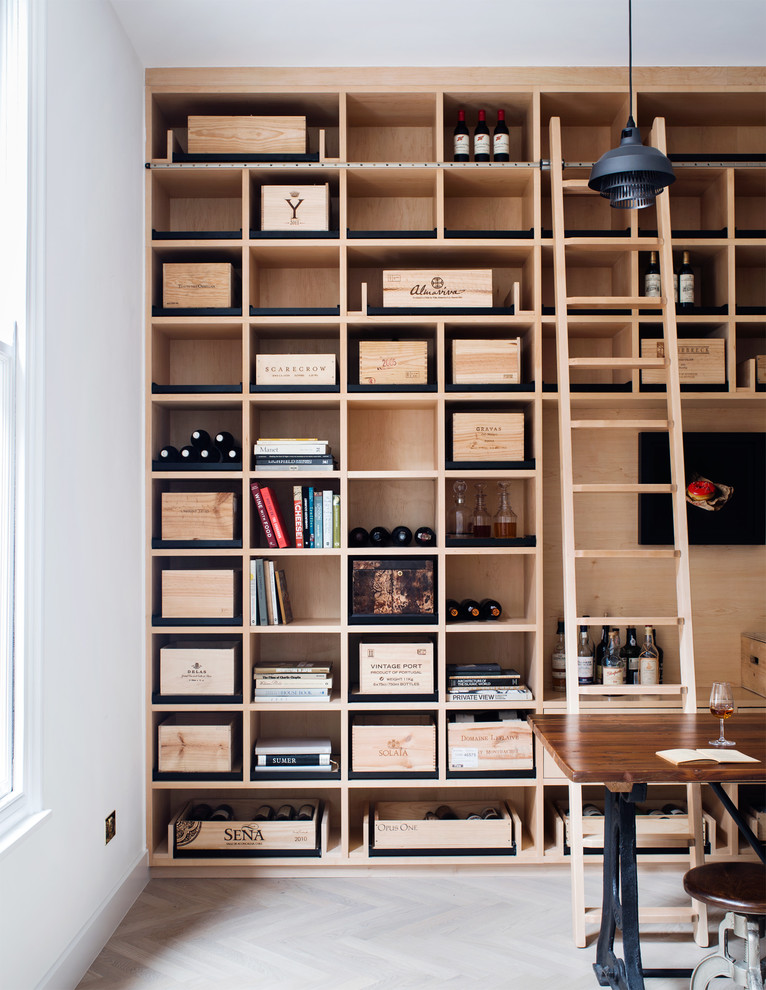 This is an example of a medium sized scandi wine cellar in London with light hardwood flooring and display racks.