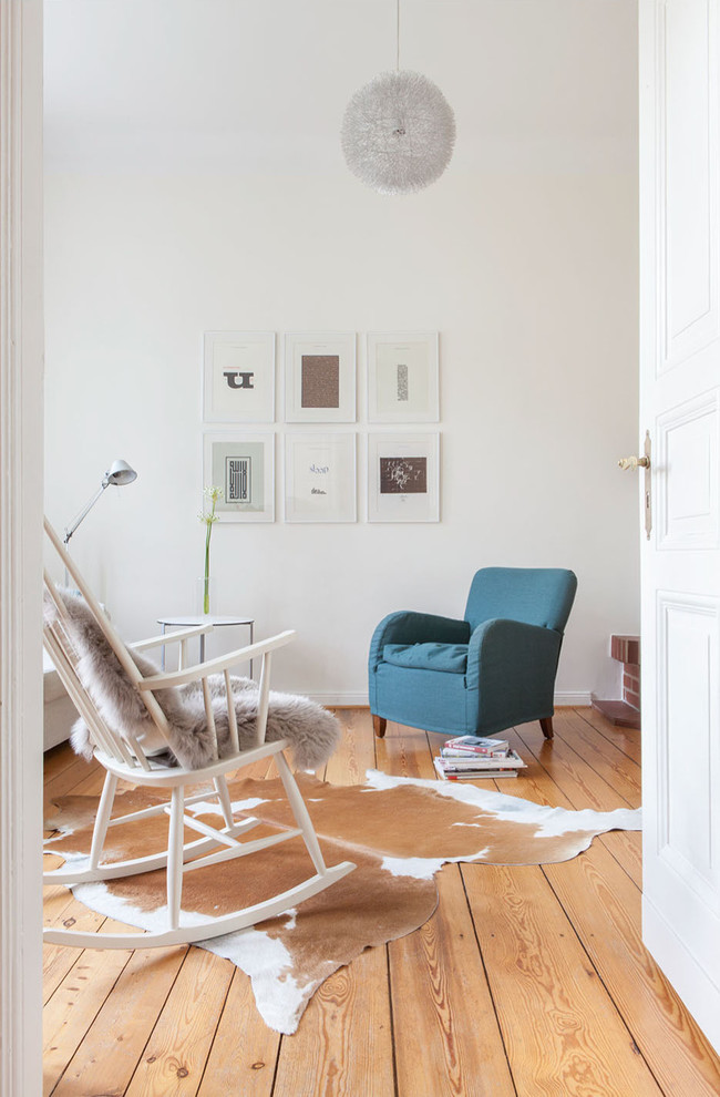 Example of a trendy formal and enclosed medium tone wood floor living room design in Berlin with white walls