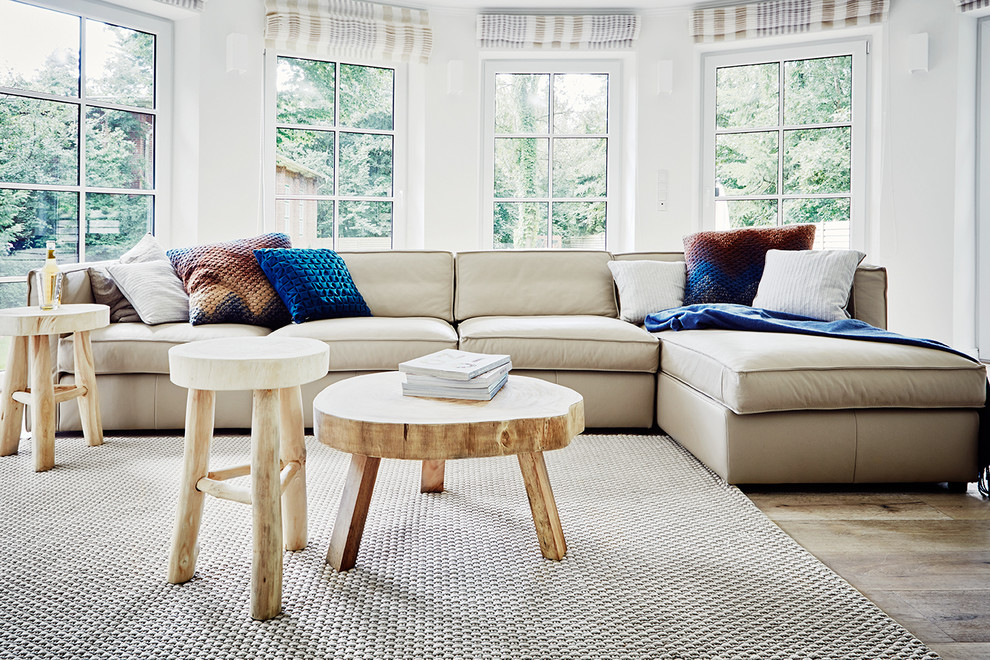 Inspiration for a mid-sized scandinavian light wood floor family room remodel in Other with white walls and no fireplace