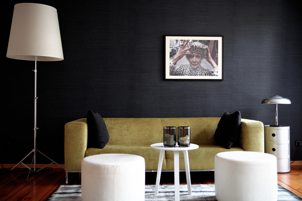 Example of a mid-sized trendy light wood floor family room design in Berlin with black walls