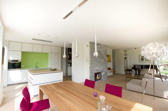 Foto de salón abierto, grande, sin televisor, con paredes blancas, suelo de madera clara, chimenea tradicional y marco de chimenea de piedra