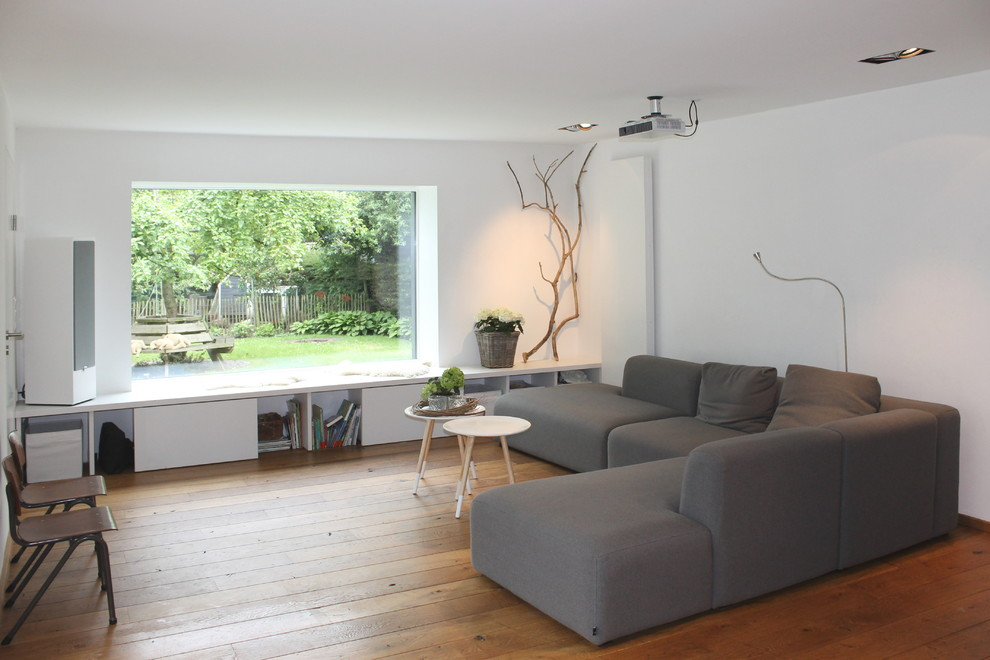 Example of a mid-sized danish medium tone wood floor family room design in Other with white walls and no fireplace