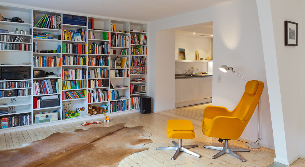 Family room library - mid-sized contemporary open concept light wood floor family room library idea in Cologne with white walls, no fireplace and no tv