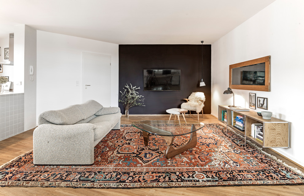Family room library - mid-sized eclectic loft-style medium tone wood floor and brown floor family room library idea in Hamburg with black walls, a wall-mounted tv and no fireplace