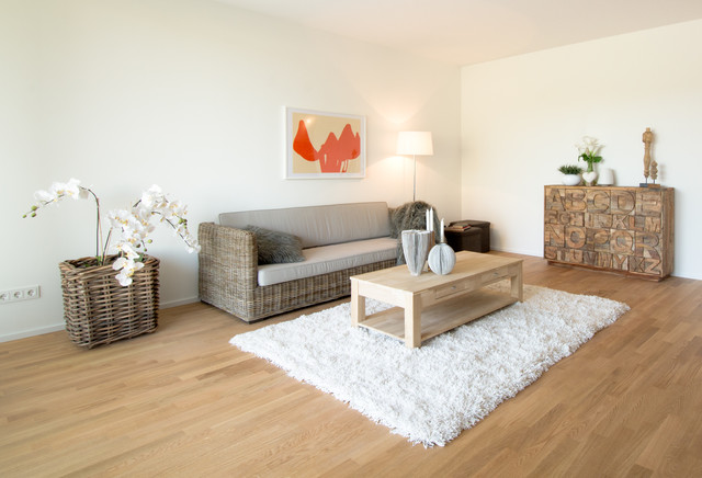 Family room - mid-sized contemporary medium tone wood floor family room idea in Essen with white walls