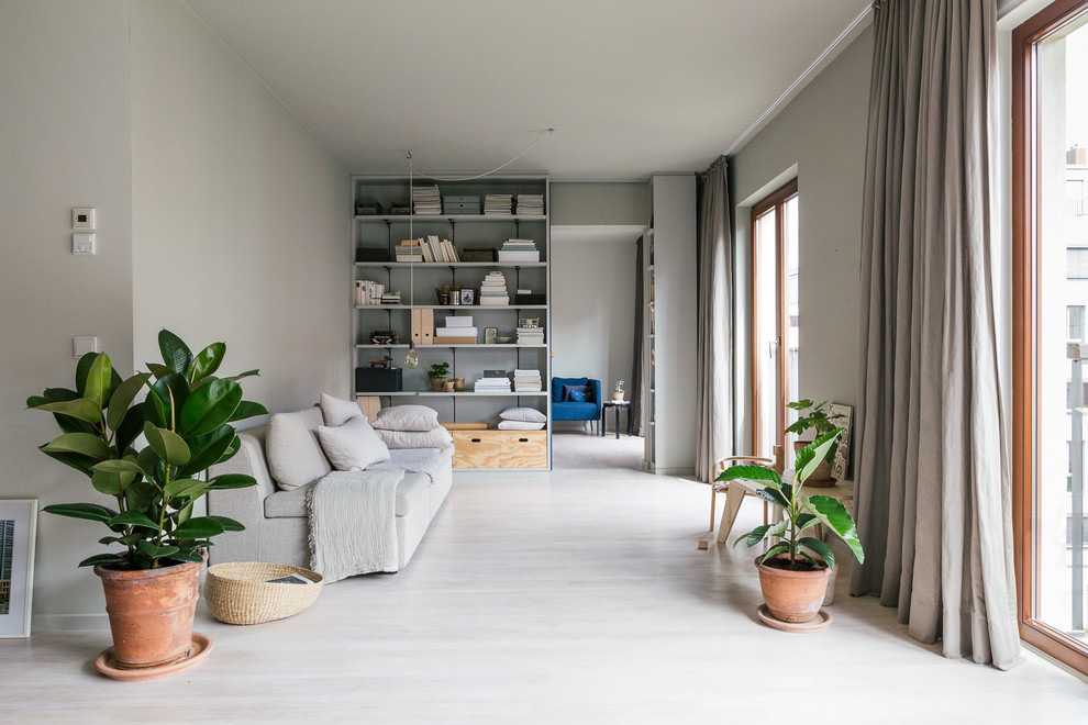 Mid-sized danish open concept light wood floor living room library photo in Berlin with gray walls and no tv