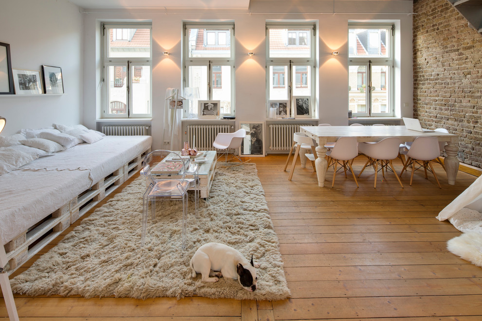 Example of a mid-sized urban open concept medium tone wood floor living room design in Cologne with white walls and no fireplace