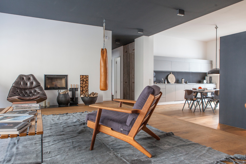 Inspiration for a mid-sized scandinavian open concept medium tone wood floor living room remodel in Berlin with white walls, a standard fireplace and a plaster fireplace