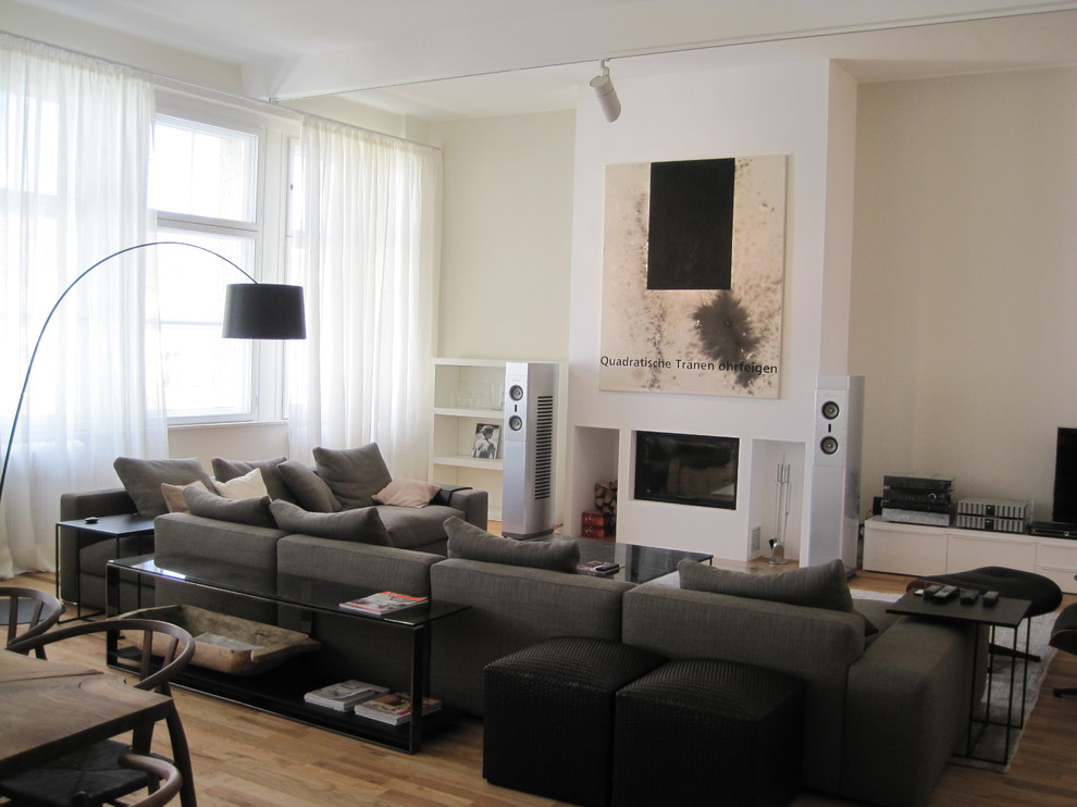 Mid-sized trendy open concept medium tone wood floor family room photo in Berlin with white walls, a standard fireplace, a plaster fireplace and no tv