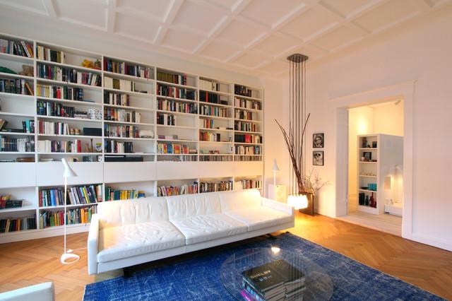 Exempel på ett stort nordiskt avskilt allrum, med vita väggar, mellanmörkt trägolv och ett bibliotek