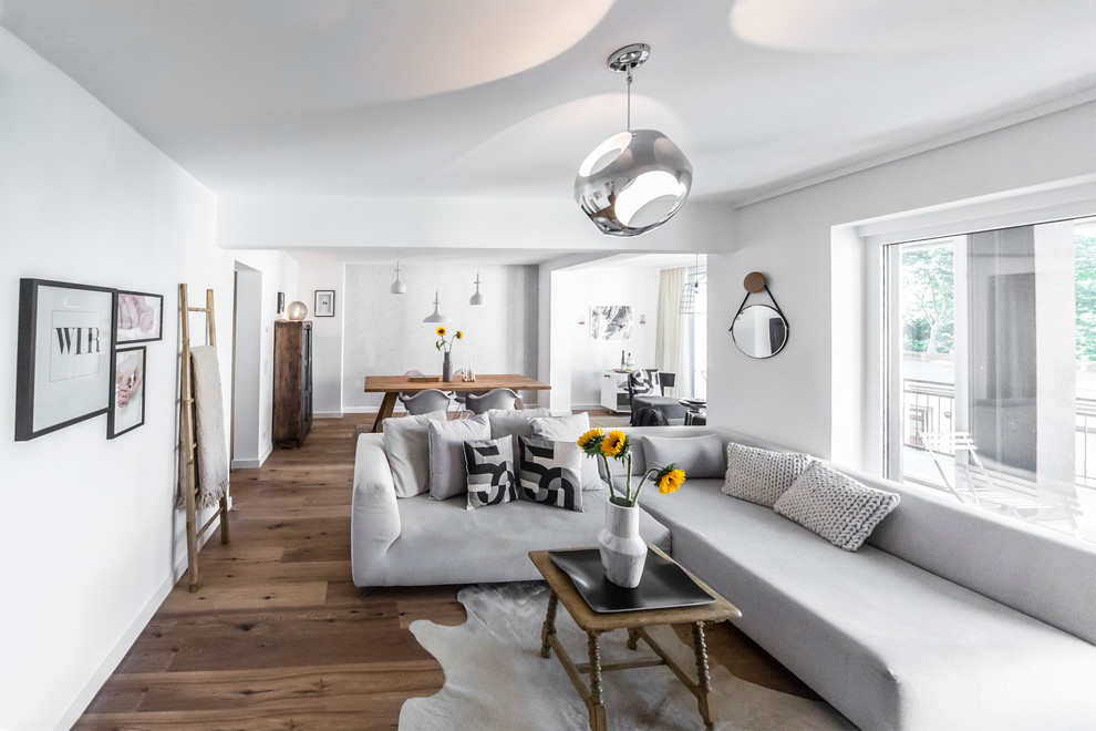 Example of a large danish open concept medium tone wood floor living room design in Dusseldorf with white walls and no fireplace