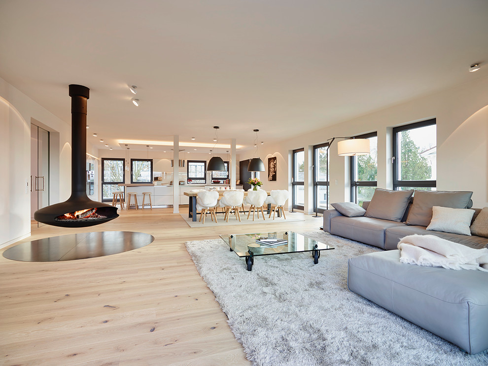 Inspiration for a huge contemporary open concept light wood floor living room remodel in Frankfurt with white walls and a hanging fireplace