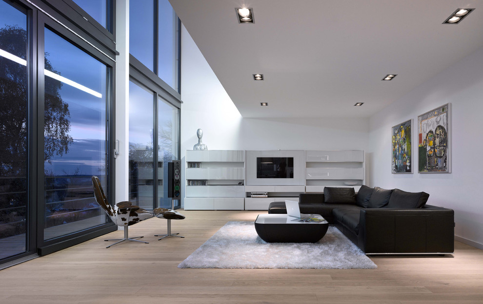 Inspiration for a large contemporary formal and open concept medium tone wood floor living room remodel in Stuttgart with white walls, a media wall and no fireplace