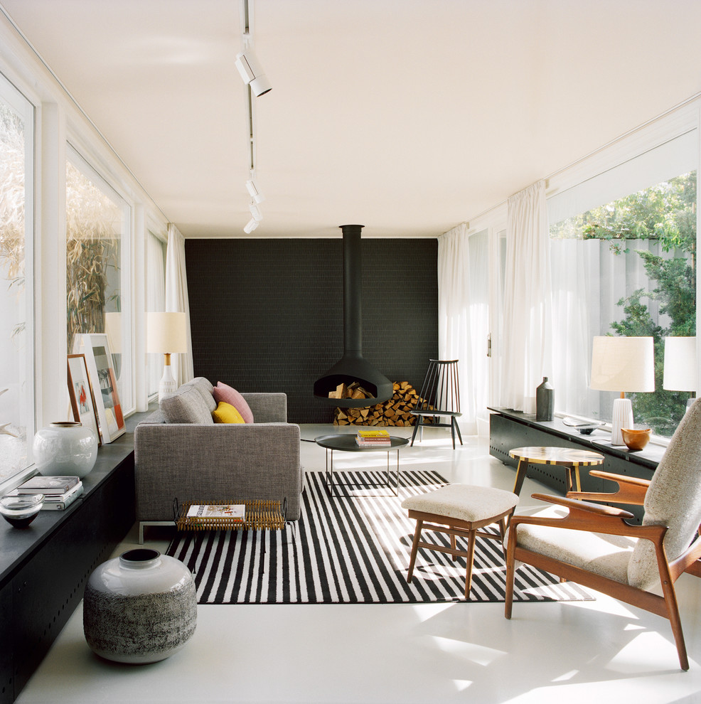 Large danish enclosed living room photo in Berlin with black walls, a hanging fireplace and a metal fireplace